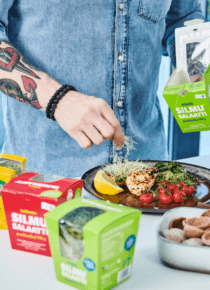 Juha Larm asettelee lautaselle Silmusalaattia annoksen päälle, jossa on kanafilettä ja uuniversoja sitruunalohkojen kera.