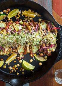 Flank steak -täytteiset tacot rivissä isossa vuoassa, koristeltuna limelohkoilla