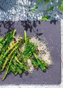 grillatut broccolinit Silmusalaatti-pedill litteän tarjoilukiven päällä.