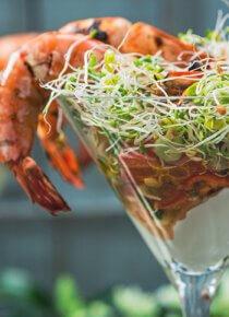 Jättikatkarapu-cocktail korkeassa lasissa, pöydällä kaksi annosta