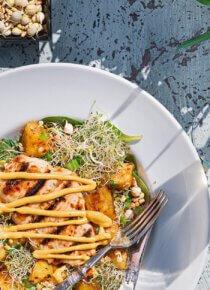 Grillattu kanasalaatti lautasella terassipöydällä, sivussa viinilasillinen ja kulhossa Rouskuvaa Silmusalaattia