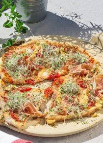Grillattu pizza pizzakiven päällä terassipöydällä