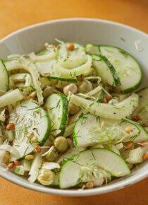 Fenkoli-kurkku-salaatti valkoisessa kulhossa keskellä kuvaa, oranssilla taustalla, oikeassa reunassa kokonainen fenkoli vasemmassa alareunassa tillipuntti